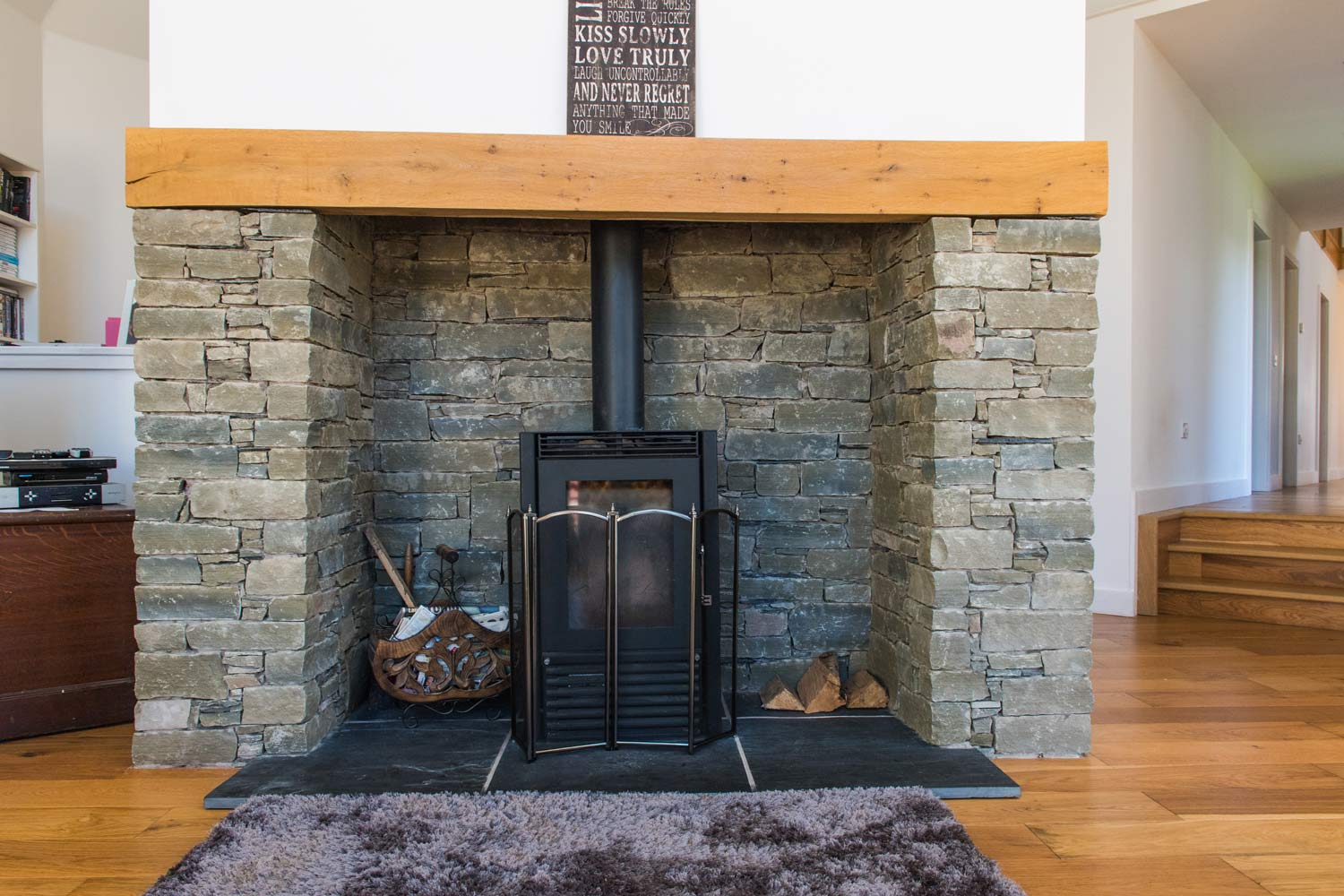 A natural stone surround for a wood burner, compliments the contemporary building